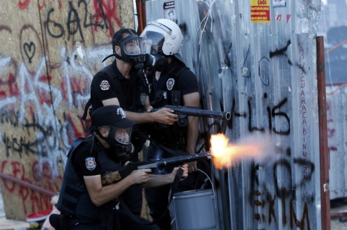 A riot policeman fires teargas during a protest at Taksim Square in Istanbul