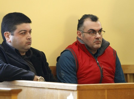 Defendants Epaminondas Korkoneas and Vassilis Saraliotis wait for their trial to start inside a court hall in Amfissa town