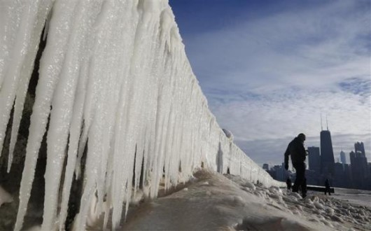 Man walks beside frozen wall on a beach in Chicago