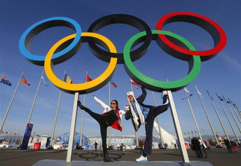 People pose for a picture in front of the Olympic rings at the Olympic Park