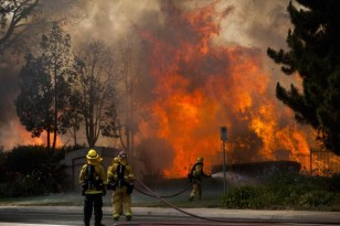 Firefighters battle the so-called Poinsettia Fire in Carlsbad, California