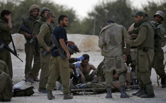 Israeli soldiers, wounded during Israel's offensive in Gaza, are treated before being evacuated by military ambulance near the border with Gaza