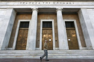 An elderly man walks outside the Bank of Greece in Athens