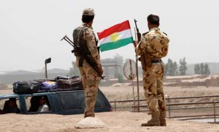 Members of the Kurdish security forces stand at a checkpoint during an intensive security deployment on the outskirts of Kirkuk