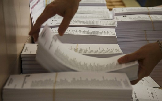 A worker piles up ballots inside a polling station on the eve of  Spanish regional and municipal elections in Madrid