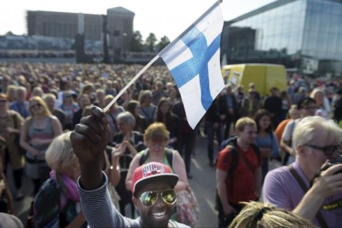 Mire Ibrahim waves the Finnish flag during a demonstration against racism where an estimated 15,000 people attended in Helsinki, Finland