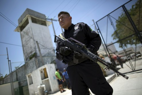 A riot policeman stands guard outside the jail during a clash of rival groups in the prison of Cancun