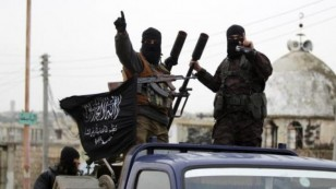 Members of al Qaeda's Nusra Front gesture as they drive in a convoy touring villages in the southern countryside of Idlib