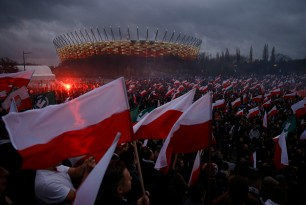 Protesters light flares and carry Polish flags during a demonstration in Warsaw