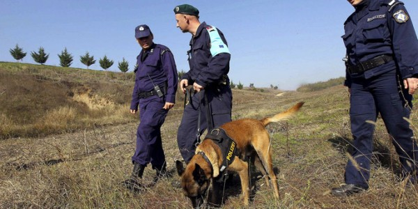 File photo of Greek border policemen, a patrol dog and an officer of Frontex border agency patrolling across border line with Turkey, near Orestiada