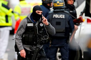 A member of the French judicial police unit speaks on the phone at the raid scene in Saint-Denis