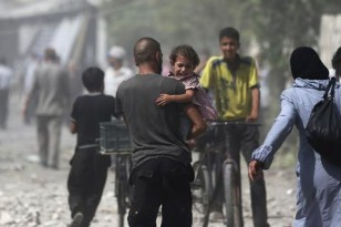 Man carries a girl reacting at a site hit by what activists said were air strikes by forces loyal to Syria's President Bashar al-Assad on a marketplace in the Douma neighborhood of Damascus, Syria