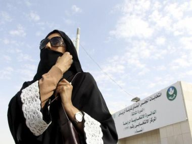 Saudi woman leaves a polling station after casting her vote during municipal elections, in Riyadh
