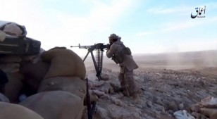 An Islamic State fighter fires a weapon in this still image taken from a video said to be taken on the outskirts of Palmyra