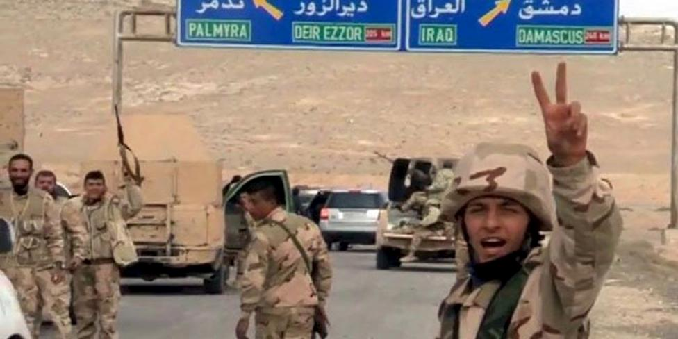 Forces loyal to Syria's President Bashar al-Assad gesture as they advance into the historic city of Palmyra