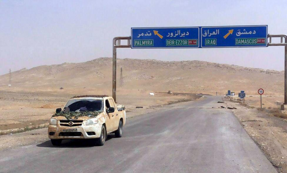 A vehicle drives near a road sign that shows the direction to the historic city of Palmyra