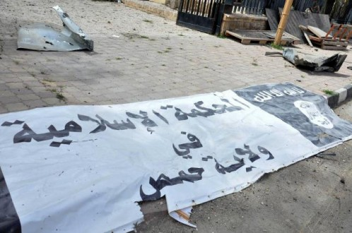 A banner belonging to the Islamic court of the Islamic State is seen on the ground after forces loyal to Syria's President Bashar al-Assad recaptured Palmyra city, in Homs Governorate
