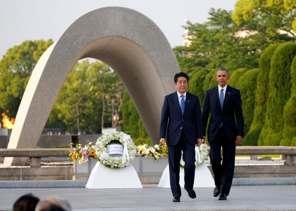 U.S. President Barack Obama and Japanese Prime Minister Shinzo Abe walk in front of a cenotaph after they laid wreaths at Hiroshima Peace Memorial Park in Hiroshima, Japan
