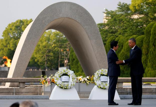 U.S. President Barack Obama (R) puts his arm around Japanese Prime Minister Shinzo Abe after they laid wreaths in front of a cenotaph at Hiroshima Peace Memorial Park in Hiroshima, Japan