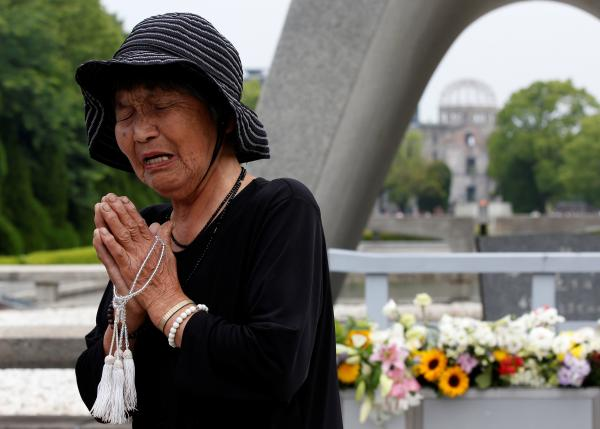 Ikegami, 84, prays in front of the cenotaph for the victims of the 1945 atomic bombing, at Peace Memorial Park in Hiroshima
