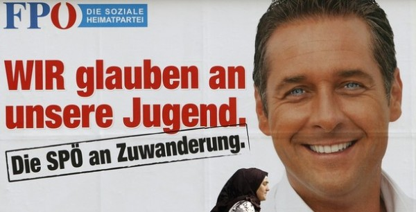 A woman passes a billboard depicting Strache, top candidate of the Austrian Freedom Party, in Vienna