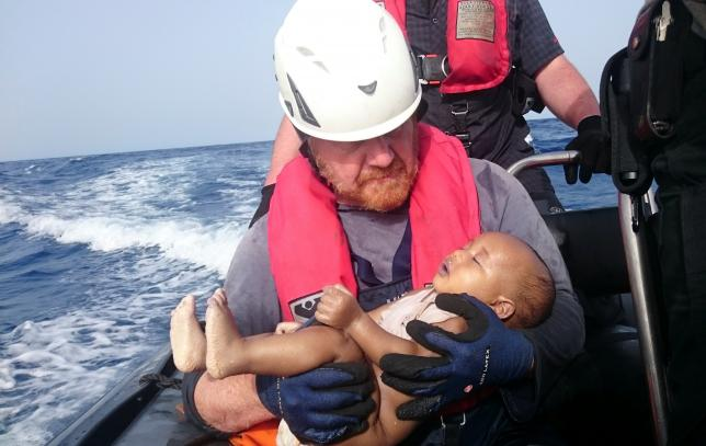 A German rescuer from the humanitarian organisation Sea-Watch holds drowned migrant baby of the Libyan cost