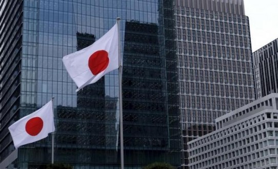 Japanese national flags flutter in front of buildings at Tokyo's business district