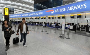 Travellers walk through departure lounge at Heathrow Airport in London