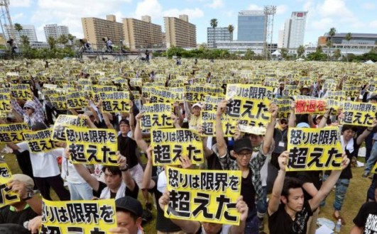 Protesters raise placards during a rally against on Japan's southern island of Okinawa