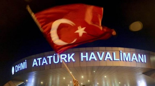 A man waves a Turkish flag in front of Ataturk Airport during an attempted coup in Istanbul