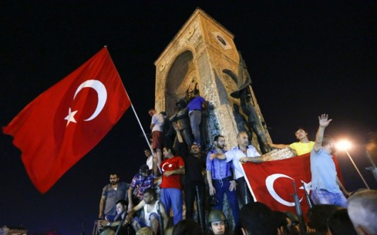 People wave flags as they demonstrate in the Taksim Square in Istanbul