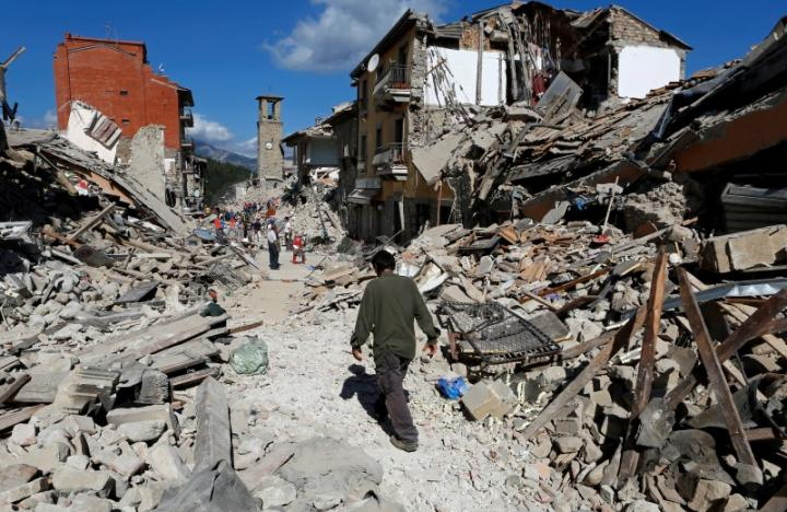 A man walks amidst rubble following an earthquake in Pescara del Tronto