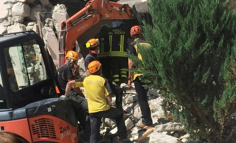 Rescuers work at a collapsed house following an earthquake in Accumoli di Rieti