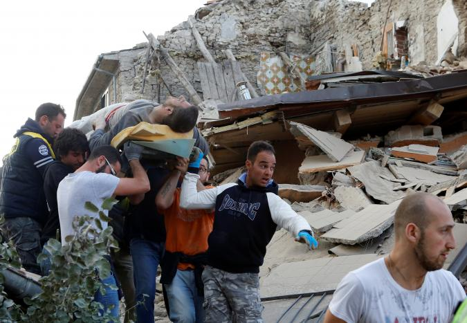 A man is carried away after having been rescued alive from the ruins following an earthquake in Amatrice