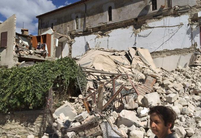 A woman stands in front of a collapsed house following an earthquake in Accumuli di Rieti