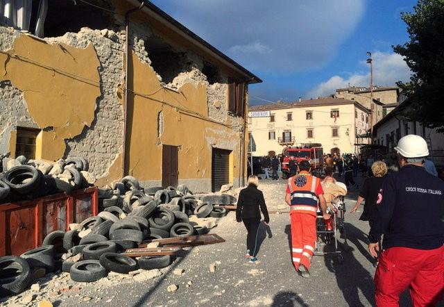 Rescuers and people walk along a road following an earthquake in Accumoli di Rieti, central Italy