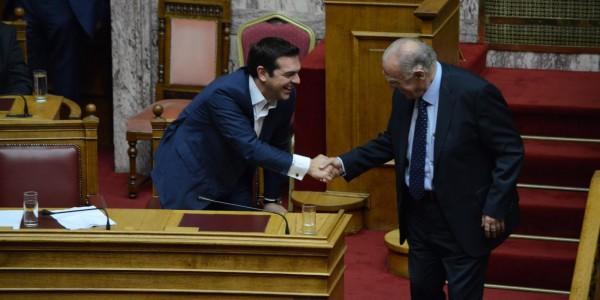 Greek Prime Minister Alexis Tsipras (left) greets Vassilis
