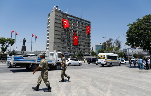 Turkish soldiers walk past by the police headquarters in Ankara