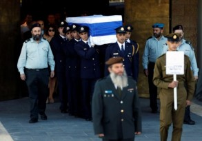 Members of the Knesset guard carry the flag-draped coffin of former Israeli President Shimon Peres, during a ceremony at the Knesset, Israeli Parliament, before it is transported to Mount Herzl Cemetery ahead of his funeral in Jerusalem