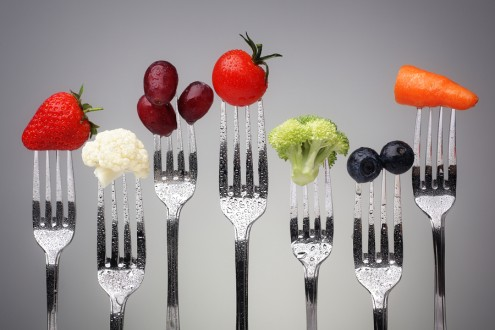 Fruit and vegetable of silver forks against a grey background co