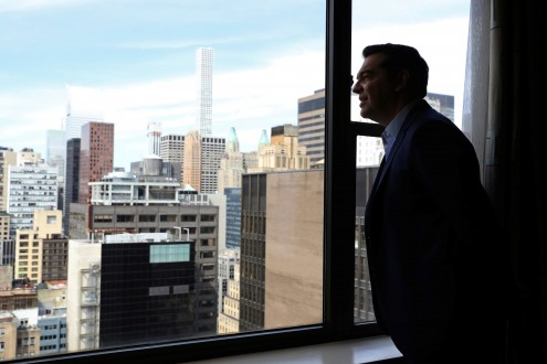 Greek PM Alexis Tsipras looks out from a hotel window on the sidelines of the United Nations General Assembly in Manhattan, New York