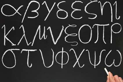 A teacher writing the Greek alphabet on a blackboard.