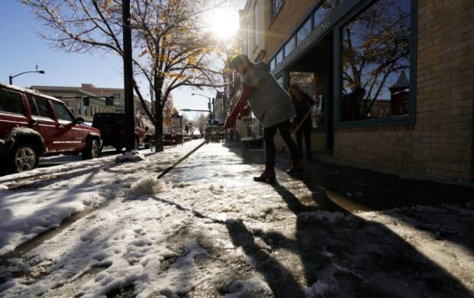 Lynn Conrad scrapes ice off the sidewalk in front of her Baby Doe's clothing store in the aftermath of the Denver area's first snowstorm of the season in Golden