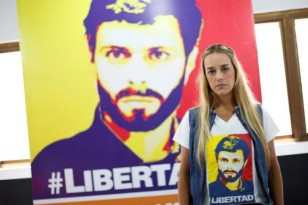 Lilian Tintori, wife of jailed Venezuelan opposition leader Leopoldo Lopez, poses for a picture in front of a poster depicting her husband at the office of the party Popular Will in Caracas